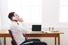 Potomstwo koncentrujący męski administrator w koszula mobilną rozmowę w nowożytnym białym biurze Fotografia Royalty Free