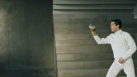 Potomstwo koncentrujący szermierza mężczyzna stażowy fechtunek ćwiczy w studiu indoors