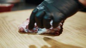 Potomstwo kucharz stawia świeżego mięso w na pokładzie kuchni w restauraci zbiory wideo
