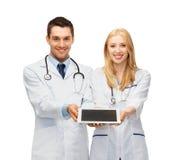 Potomstwo lekarki pokazuje pastylka komputer osobistego Zdjęcie Stock