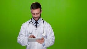 Potomstwo lekarki spojrzenia przy obrazkami na pastylka komputerze osobistym zielony ekran zdjęcie wideo