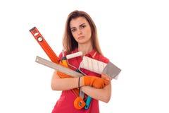 Potomstwo męczący brunetki kobiety budowniczy w mundurze z narzędziami w jej rękach robi reovations odizolowywającym na białym tl Zdjęcie Stock