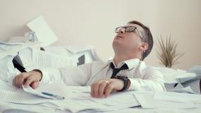Potomstwo męczący mężczyzna w szkłach siedzi w stosie papiery i znaków dokumenty Przez zmęczenia, osoba jest wzburzona i zbiory