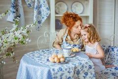 Potomstwo matka całuje jej córki przy stołem na kuchni Zdjęcia Stock