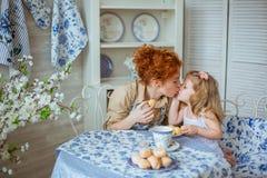 Potomstwo matka całuje jej małej córki na kuchni Obrazy Stock