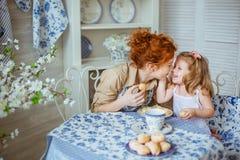 Potomstwo matka całuje jej małej córki przy biurkiem Zdjęcie Stock