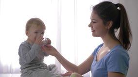 Potomstwo matka daje małemu syna szkłu woda mineralna quench pragnienie i dziecko jest bardzo roześmianym i szczęśliwym zakończen zbiory