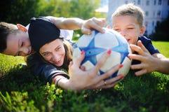 Potomstwo matka i jej chłopiec bawić się mecz piłkarskiego na pogodnym letnim dniu Zdjęcia Royalty Free