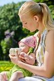 Potomstwo matka karmi dziecka od butelki obraz stock