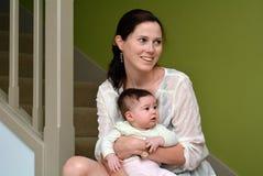 Potomstwo matka trzyma jej dziecka w domu obraz stock
