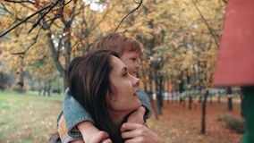 Potomstwo matki chwyty na ramionach śliczna chłopiec, chłopiec ściskają jej pobliskich ptasich dozowniki w zadziwiającym jesień p zbiory wideo