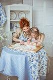 Potomstwo matki pomoc staczać się ciasto jej mała córka Obraz Stock