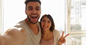 Potomstwo Mieszająca Biegowa para Bierze Selfie fotografię Nad Dużym Nadokiennym ranku światłem słonecznym, Szczęśliwego Latynosk zbiory wideo