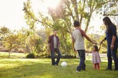 Potomstwo mieszająca biegowa rodzina bawić się z piłką w parku, backlit obrazy stock