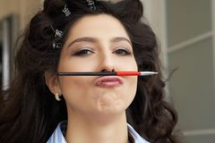 Potomstwo model trzyma makeup muśnięcie w postaci wąsy w fryzury i makeup salonie mała zabawa podczas długiego Obrazy Royalty Free