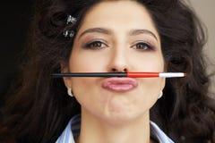 Potomstwo model trzyma makeup muśnięcie w postaci wąsy w fryzury i makeup salonie mała zabawa podczas długiego Zdjęcia Royalty Free