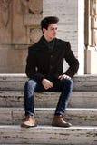Potomstwo modela mężczyzna obsiadanie na marmurowych krokach Zdjęcie Royalty Free