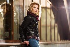 Potomstwo mody blond kobieta w skórzanej kurtce przy centrum handlowego okno obrazy stock
