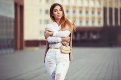 Potomstwo mody kobieta chodzi w miasto ulicie w białych koszulowych i rozdzierających cajgach zdjęcie stock