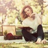 Potomstwo mody kobieta czyta ksi??k? w miasto parku obrazy royalty free