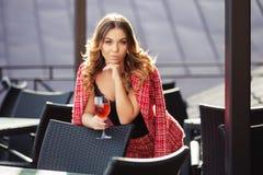 Potomstwo mody kobieta w czerwonej tweed kurtce i skróty nadajemy się przy chodniczek kawiarnią Zdjęcia Royalty Free