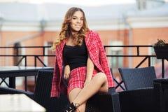 Potomstwo mody kobieta w czerwonej tweed kurtce i skróty nadajemy się przy chodniczek kawiarnią Obrazy Royalty Free