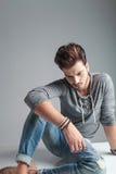 Potomstwo mody mężczyzna patrzeje w dół podczas gdy relaksujący Fotografia Stock