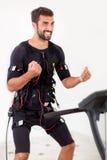 Potomstwo napadu mężczyzna ćwiczenia bicepsy fryzują na electro mięśniowym stimulat zdjęcia royalty free