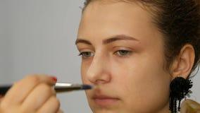 Potomstwo nastolatka dosyć miedzianowłosa dziewczyna stosuje concealer z dodatku specjalnego muśnięciem na jej twarzy zbiory