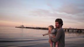 Potomstwo ojca sztuki z małą córką na plaża śmiechach i uściśnięciach, rzucają w górę zbiory