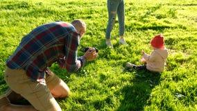 Potomstwo ojciec bierze obrazki córka w parku przy zmierzchem Szczęśliwa rodzina ma odpoczynek z dzieckiem na naturze fotografia stock