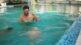 Potomstwo ojciec pokazuje jego mały syn nur pod wodą w pływackim basenie podczas gdy siedzi na granicie On zbiory wideo