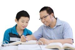 Potomstwo ojciec pomaga jego syna robi pracie domowej Zdjęcia Royalty Free