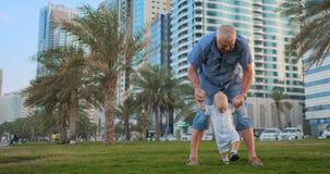 Potomstwo ojciec z dzieckiem i pierwszymi krokami Potomstwa ojcują z dzieckiem przy plenerowym learninig dla pierwszych kroki bli zbiory