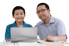 Potomstwo ojciec z jego synem studiuje wpólnie Zdjęcie Royalty Free