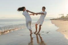 Potomstwo para bawić się na plaży Obraz Royalty Free