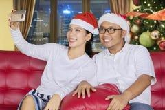 Potomstwo para bierze fotografię przy święto bożęgo narodzenia Zdjęcia Stock