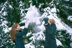 Potomstwo para cieszy się śnieg Zdjęcia Royalty Free