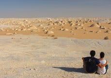 Potomstwo para cieszy się widoki po środku zadziwiającej biel pustyni Fotografia Stock