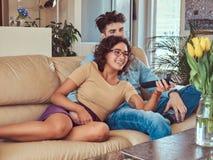 Potomstwo para cuddling podczas gdy oglądający TV w domu zdjęcia stock