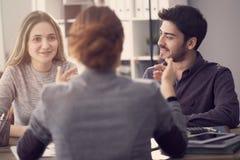 Potomstwo para dyskutuje z żeńskim agentem Obraz Stock