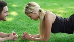 Potomstwo para flirtuje przy sprawność fizyczna treningiem plenerowym Sprawność fizyczna mężczyzna opowiada z kobietą zbiory wideo