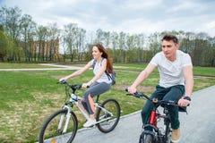 Potomstwo para iść na rowerze na słonecznym dniu w miasto parku Zdjęcia Royalty Free