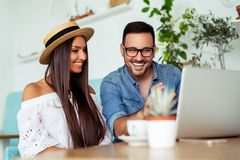 Potomstwo para jest pracująca w kawiarni na laptopie i ono uśmiecha się - Wizerunek zdjęcia stock