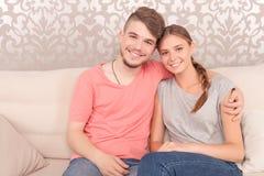 Potomstwo para jest usytuowanym na kanapie Obraz Royalty Free
