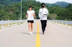 Potomstwo para jogging w parku zdrowie fizyczne fitness jogs pos?uchaj muzyki podczas gdy przeno?ne obraz stock