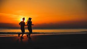 Potomstwo para: mężczyzna i kobieta biegamy wpólnie na zmierzchu na jeziorze Zdjęcia Stock