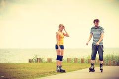 Potomstwo para na rolkowych łyżwach jedzie outdoors Obraz Royalty Free