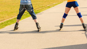 Potomstwo para na rolkowych łyżwach jedzie outdoors zdjęcie royalty free
