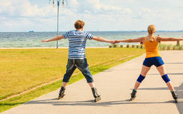 Potomstwo para na rolkowych łyżwach jedzie outdoors Zdjęcia Stock
